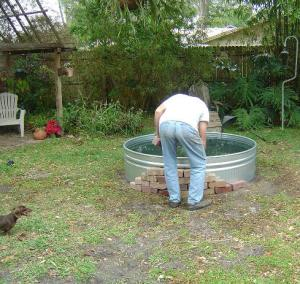 Mark enclosing galvanized water trough with brick to make goldfish pond