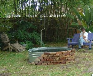 Brick enclosure around galvanized goldfish pond almost done.