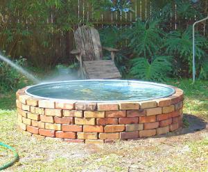 Brickwork surrounding galvanized water trough goldfish pond completed.